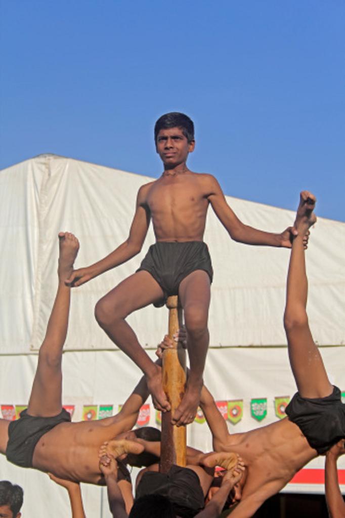 Jeunes hommes en pleine démonstration de Mallakhamba, un sport traditionnel indien