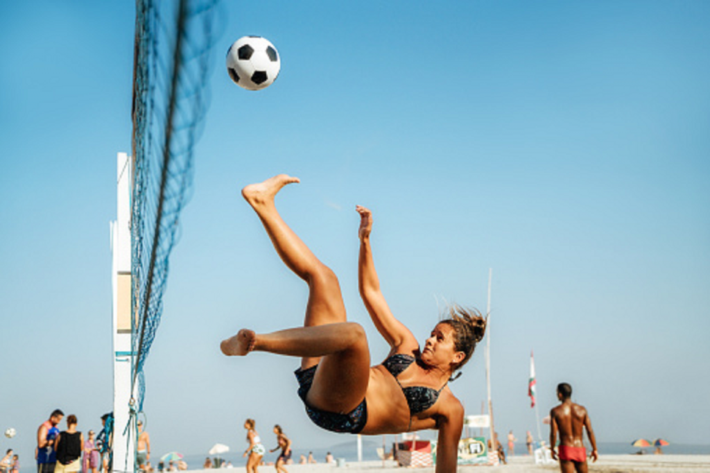 Une joueuse de footvolley se détend et frappe du pied le ballon afin de le faire passer au dessus du filet