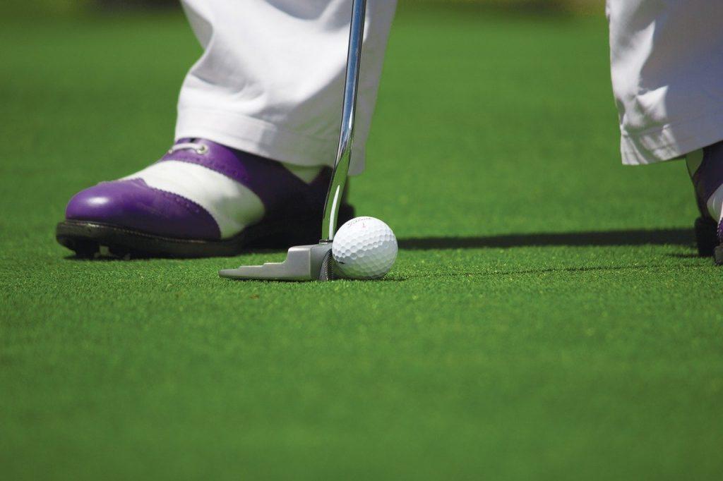 une balle de golf au pied d'un joueur